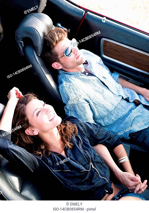 couple lying in open-topped car