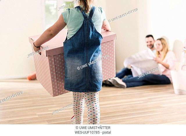 Girl carrying cardboard box in empty apartment with parents in background
