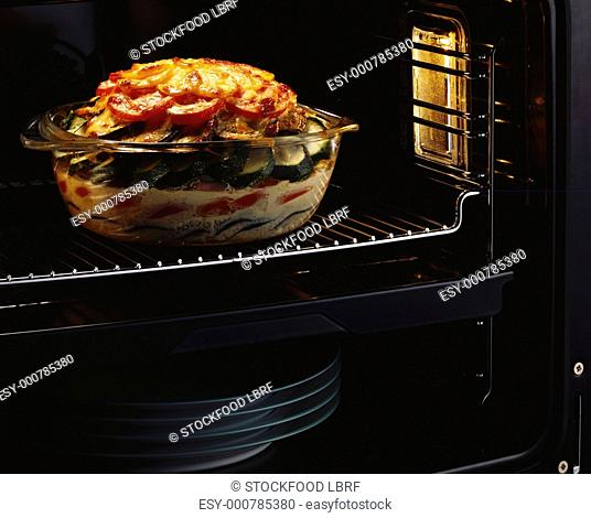 Vegetable casserole in glass dish in oven