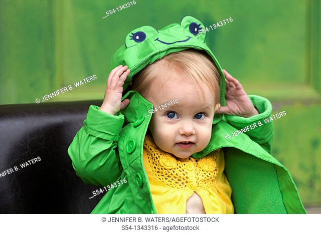 A toddler outdoors in a bright green raincoat