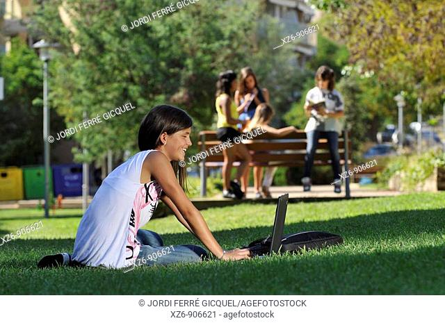 foreground of a girl using the computer in the park, while a group talk back