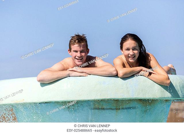 Girl Boy teenagers at beach pool summer holidays talk laughter swimming happy fun