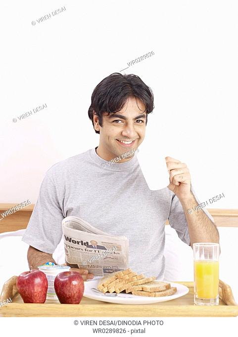 Young man holding newspaper and mug having breakfast on bed MR702V