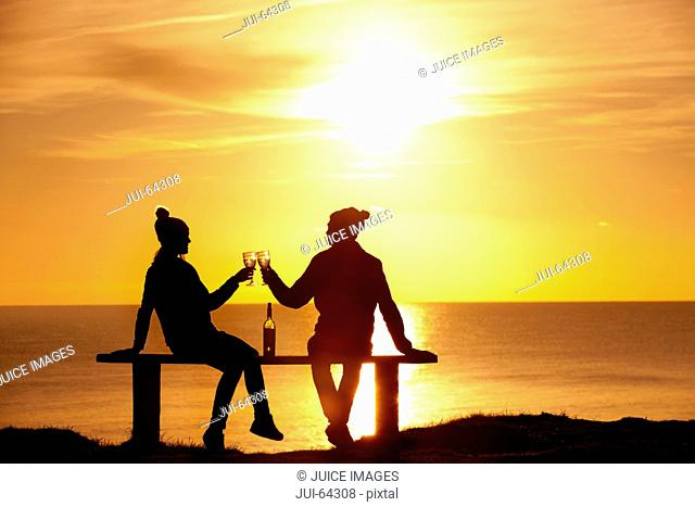 Silhouette of couple, sitting on bench and drinking glass of wine, against sunset over the ocean