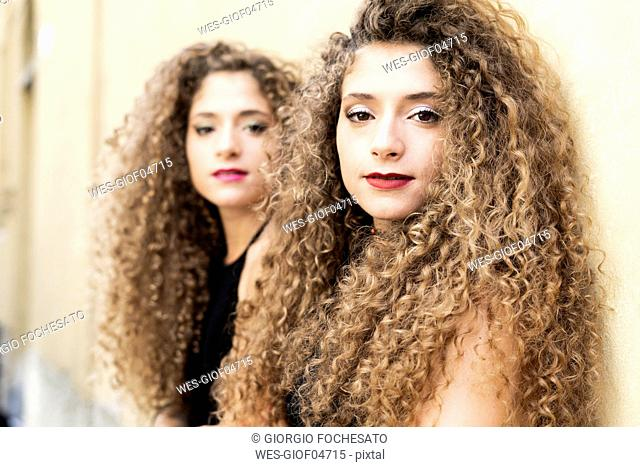 Portrait of young woman with ringlets and her twin sister in the background