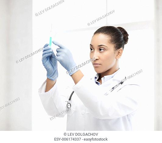 healthcare and medical concept - african doctor holding syringe with injection