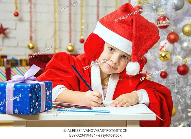 Four-year girl dressed in a red suit Santa Claus draws pencils are in a festive Christmas interior