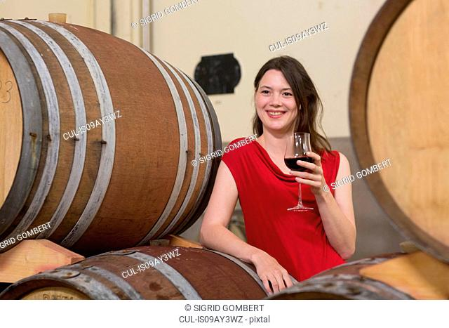 Portrait of young woman in wine cellar, leaning against wine barrel, holding glass of wine