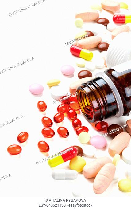Closeup shot of red capsules and colorful pills. Isolated on white background