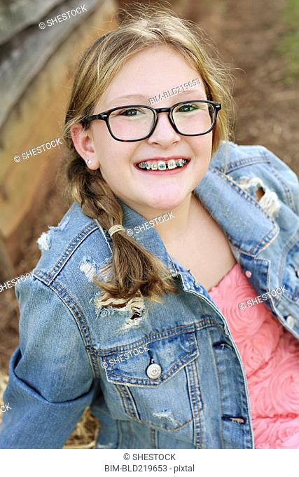 Smiling Caucasian girl with braces and eyeglasses