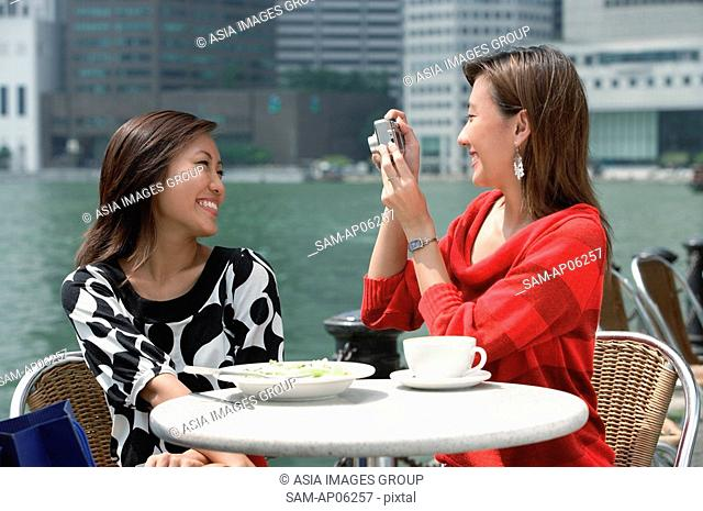 Two women at outdoor cafe, using a camera