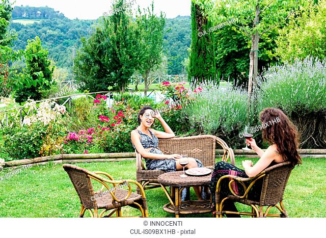 Women on wicker chairs in countryside garden, Città della Pieve, Umbria, Italy