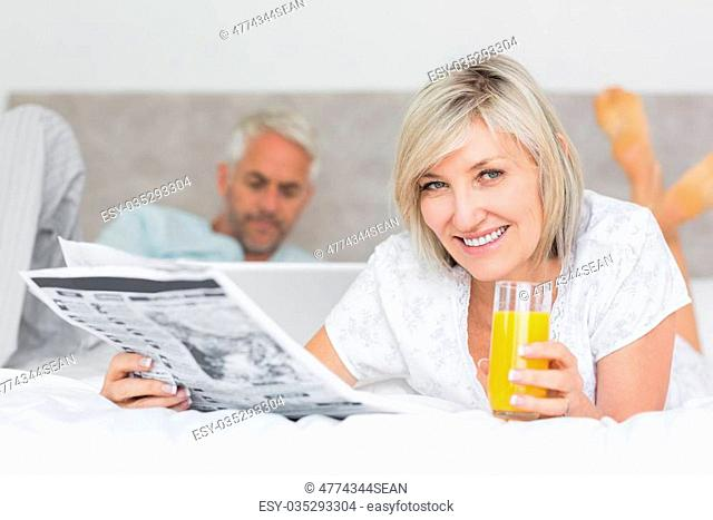 Closeup of a woman reading newspaper with man using laptop in background in bed at home