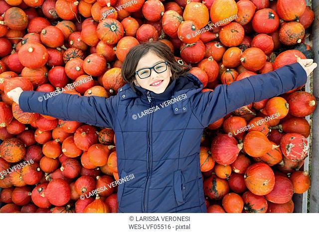 Portrait os smiling girl lying on pile of Hokkaido pumpkins