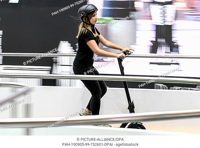 05 September 2019, Berlin: A young woman drives an electric scooter made by Segway on the second media day of the IFA technology fair