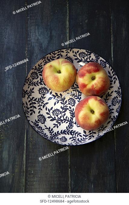 Three peaches on a plate