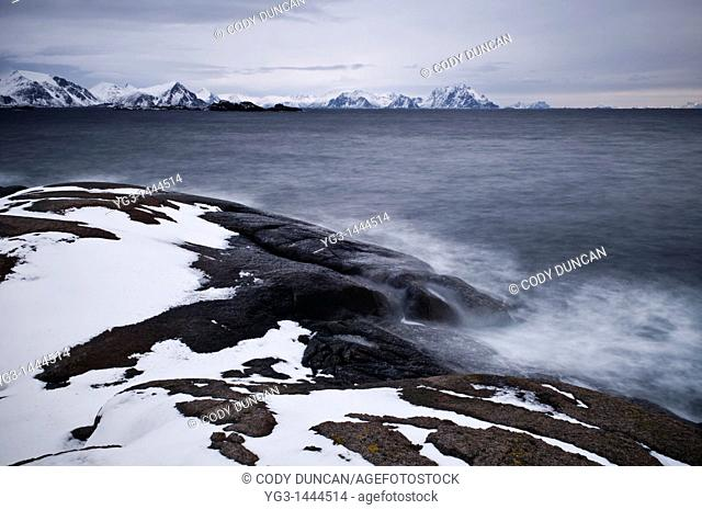 waves crash against rugged snow covered rocky coastline in winter, Stamsund, Vestvågøy, Lofoten islands, Norway