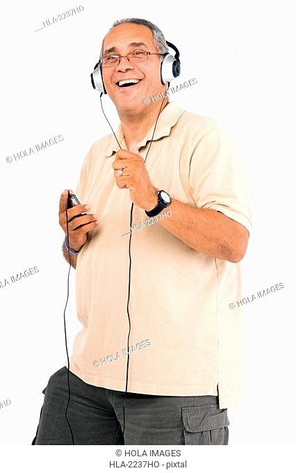 Portrait of a mature man listening to an MP3 player and laughing