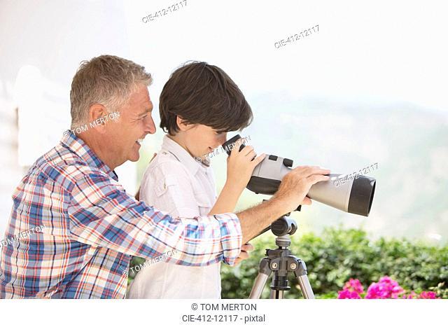Grandfather and grandson using telescope