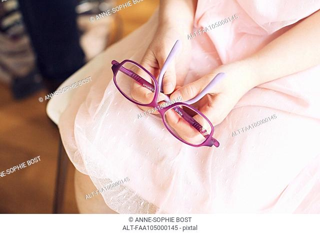 Girl holding pair of glasses on lap, cropped