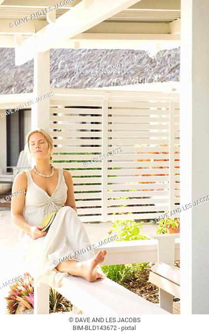 Caucasian woman relaxing on porch railing