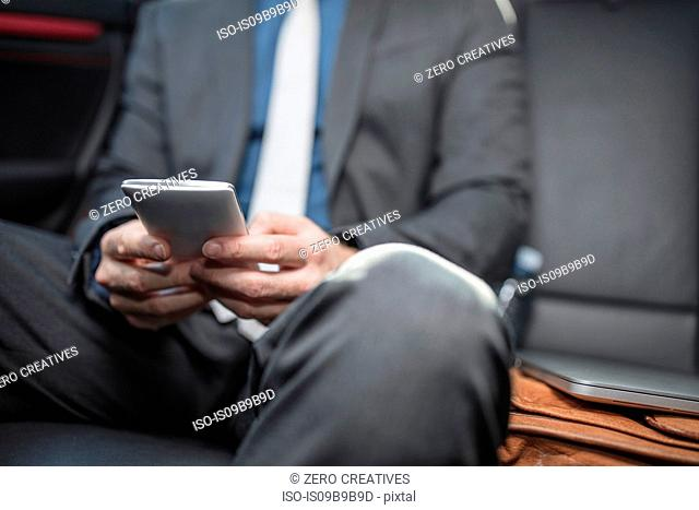 Businessman sitting in back of car, using smartphone, mid section