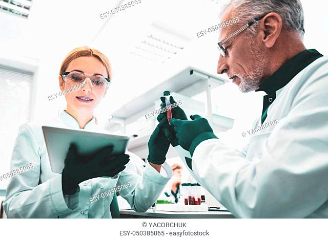 Young biologist. Young biologist using modern technologies during working in laboratory with her professional partners
