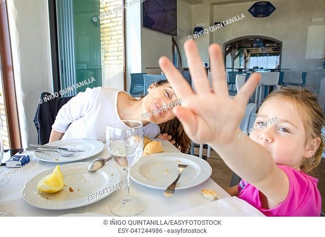 little girl four years old hiding with hand, or covering view, shutting out refusal. eating in restaurant with her mother, sitting in restaurant