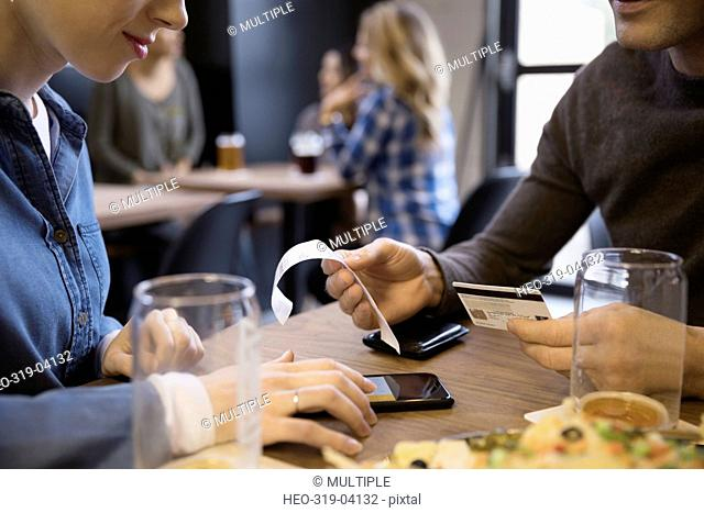 Close up couple with credit card paying bill calculating tip with smart phone in brewery restaurant