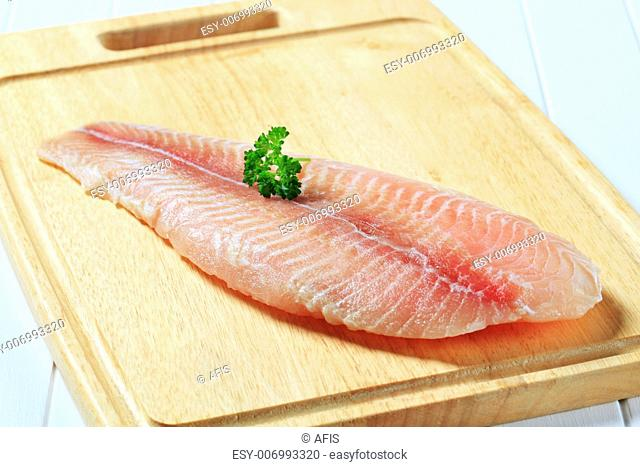 Frozen catfish fillet on cutting board
