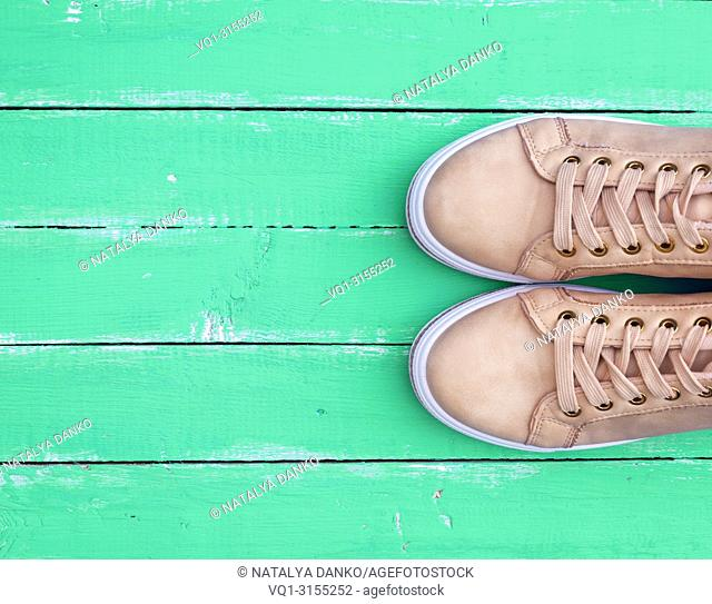 top view of a pink pair of female leather sneakers with laces on a green wooden background, copy space