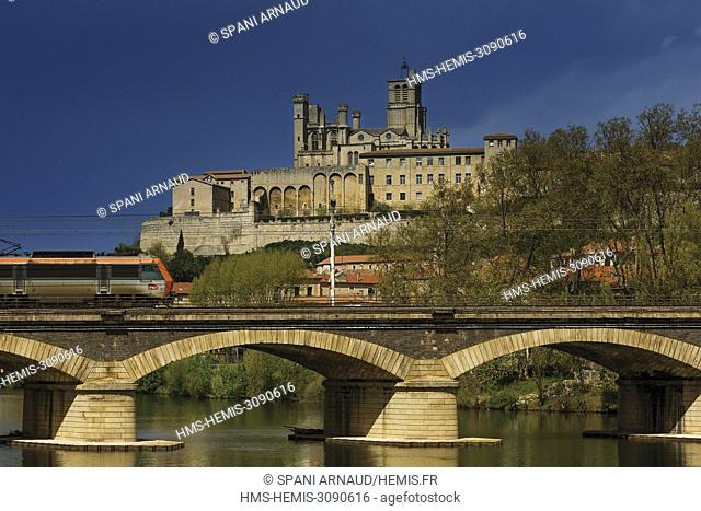 France, Herault, Beziers, cathedral Saint Nazaire and upper city under a stormy sky with a train on a bridge in the foreground