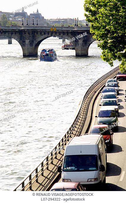 Cars and tourist boat along Seine River. Paris. France