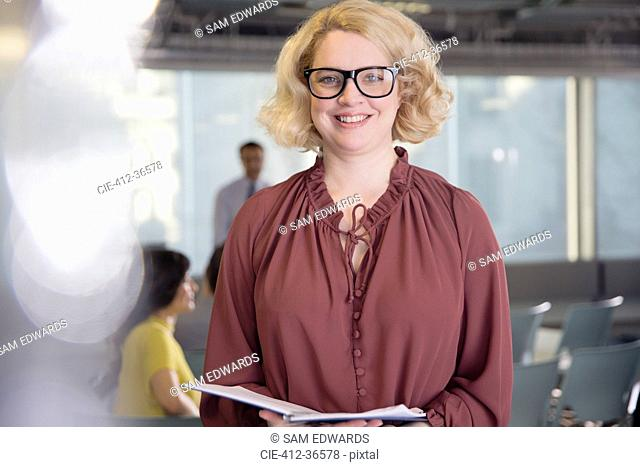 Portrait smiling, confident businesswoman with paperwork in office