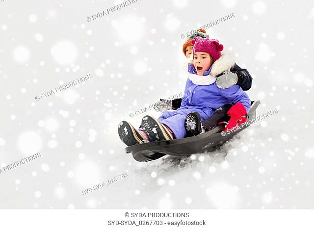 kids sliding on sled down snow hill in winter