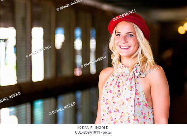 Young woman wearing red hat walking in underpass