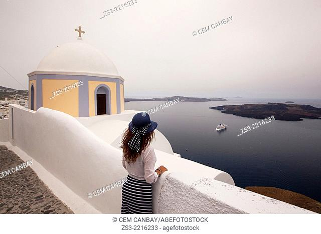 Woman in front of a yellow domed church in Fira town looking at the sea, Santorini, Cyclades Islands, Greek Islands, Greece, Europe