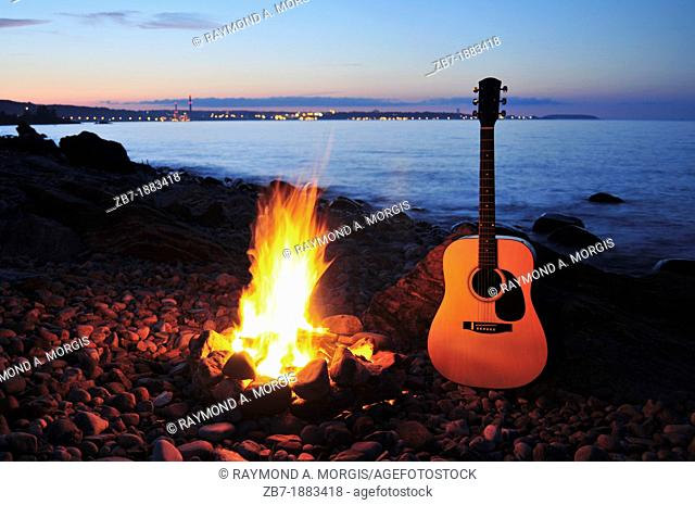 An acoustic guitar next to a campfire on a rocky shoreline