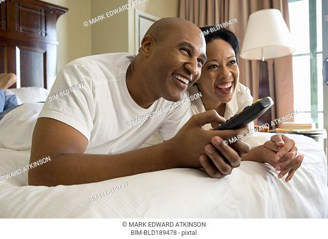 African couple in bed watching television