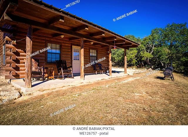 Exterior of rustic farm log house with wooden rocking chairs on the fron deck. Barbecue smoker in the front yard. Texas, USA