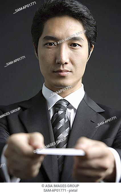 Businessman holding out business card