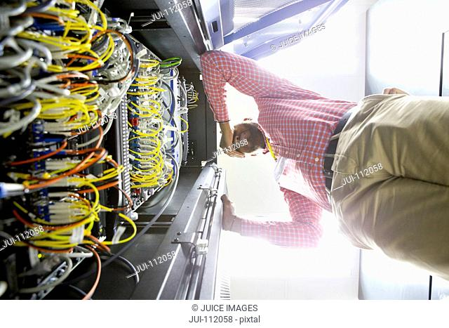 Frustrated technician checking wiring of server in data centre