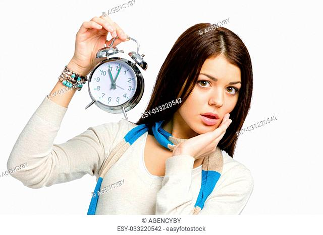 Amazed woman with alarm clock wearing colored scarf and beige pullover, isolated on white