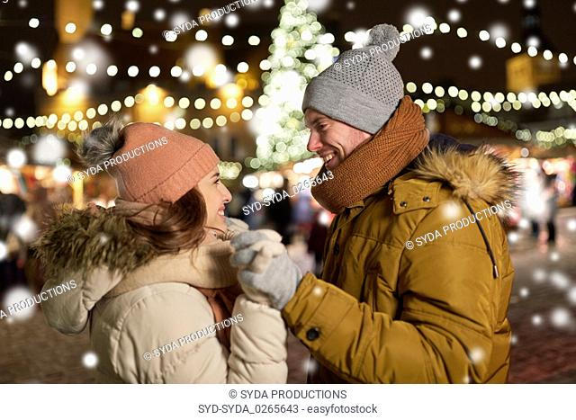 happy couple holding hands at christmas tree