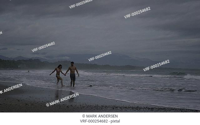 Slow motion wide panning shot of couple walking on beach / Esterillos, Puntarenas, Costa Rica