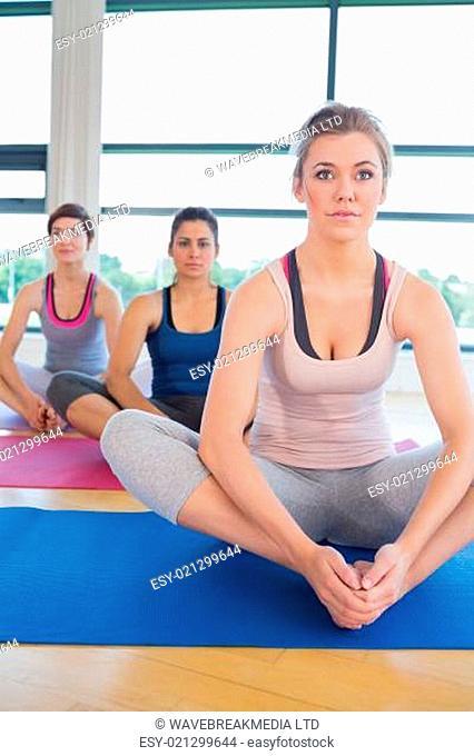 Women in bound angle yoga pose in fitness studio