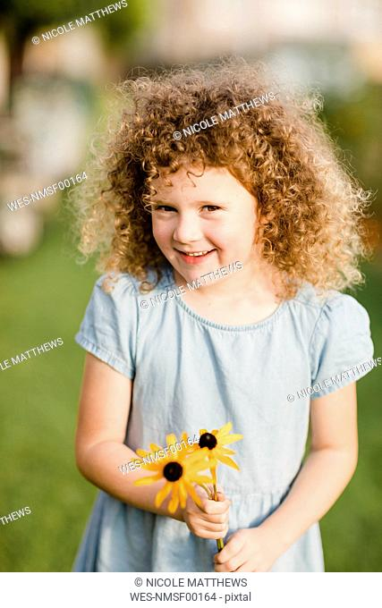 Portrait of happy little girl with picked flowers in the garden