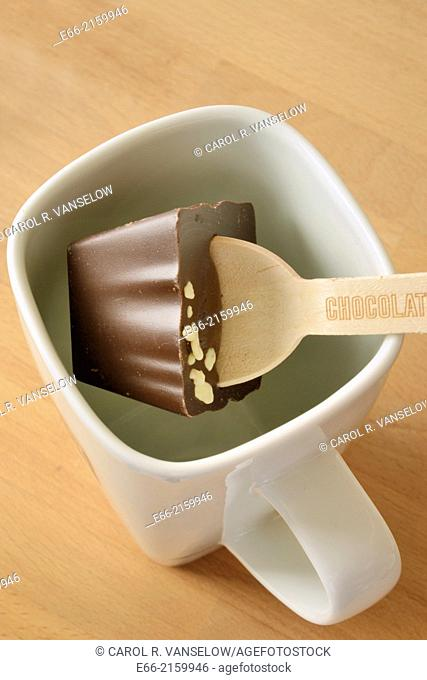 Wooden spoon with cube of chocolate for making hot coco