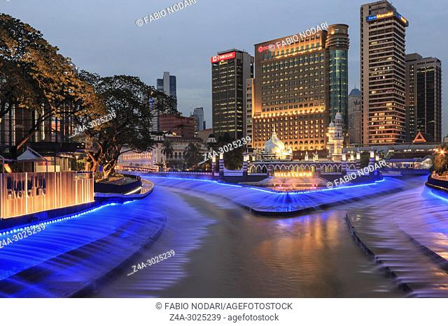 -Office buildings and Sultan Abdul Samad Jamek Mosque with water fountain lit at night on the banks of the Klang and Gombak rivers