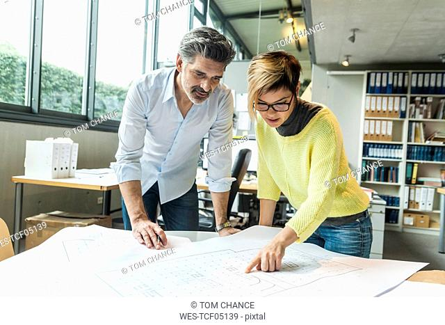 Male and female architects discussing ground plan in office
